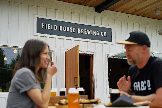 two people enjoying beer at field house brewing co. in abbotsford