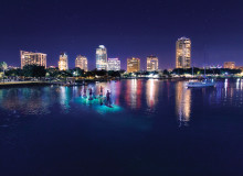 Swoop | a picture of a group of people paddleboarding in St. Petersburg Clearwater in Florida Tampa at night with glowing buildings