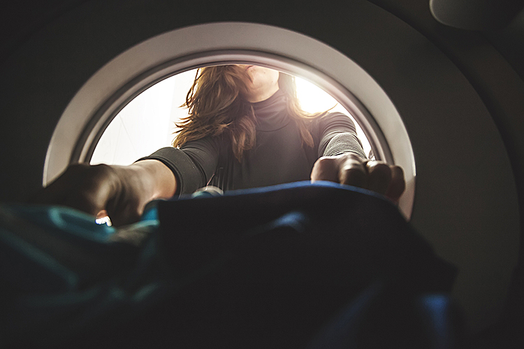 image of a hands reaching inside a washing machine.