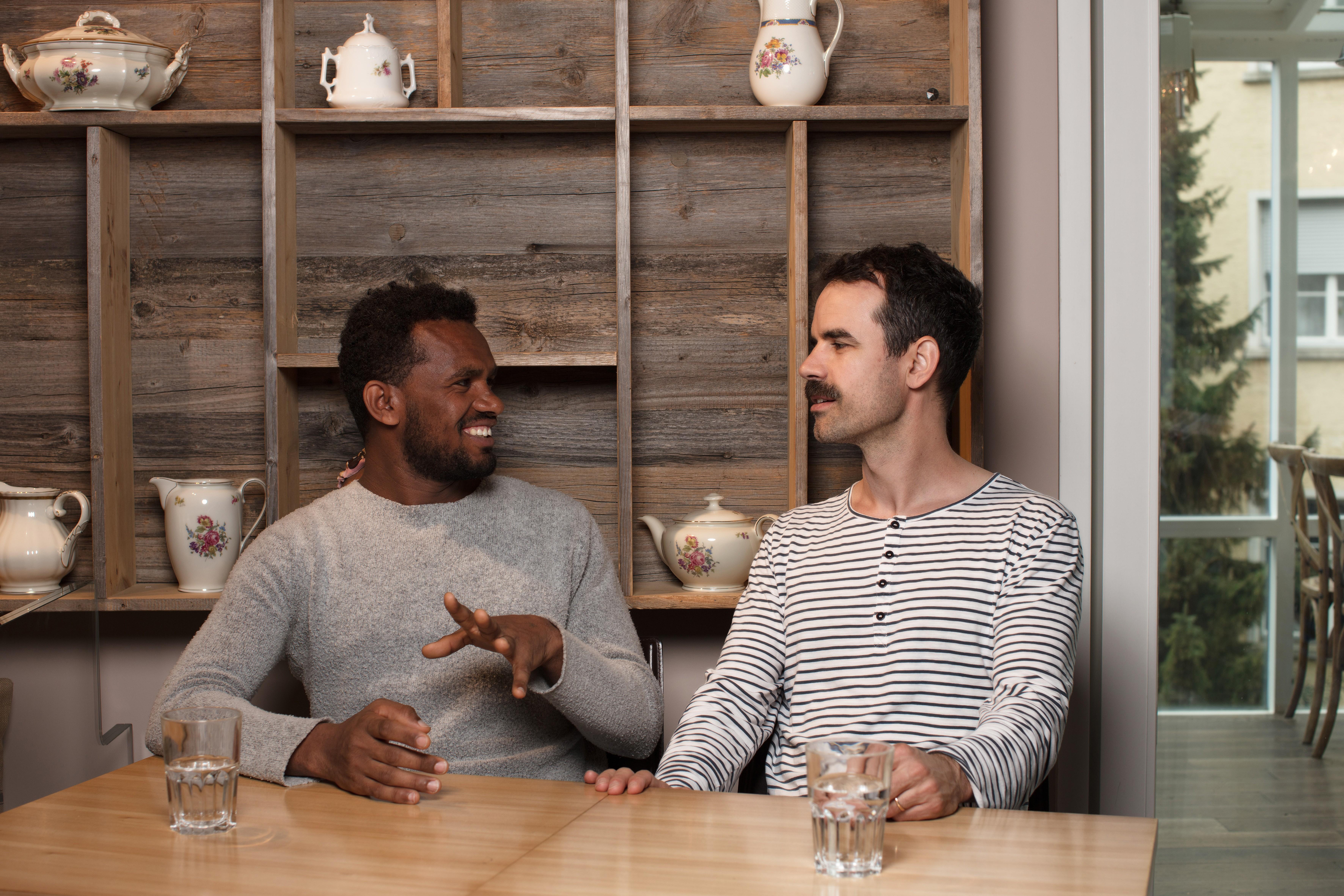 Zwei Männer trinken etwas zusammen im Café