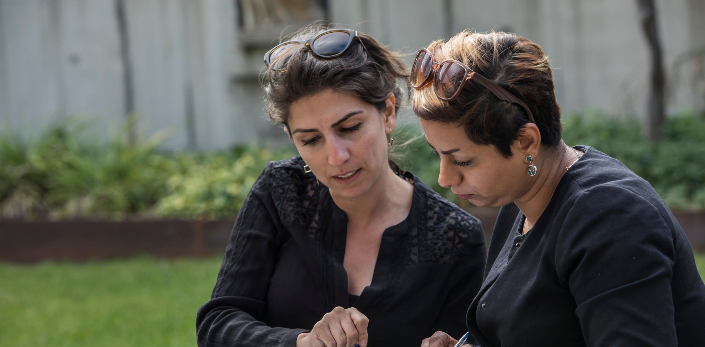 Zwei Frauen füllen gemeinsam ein Dokument aus.