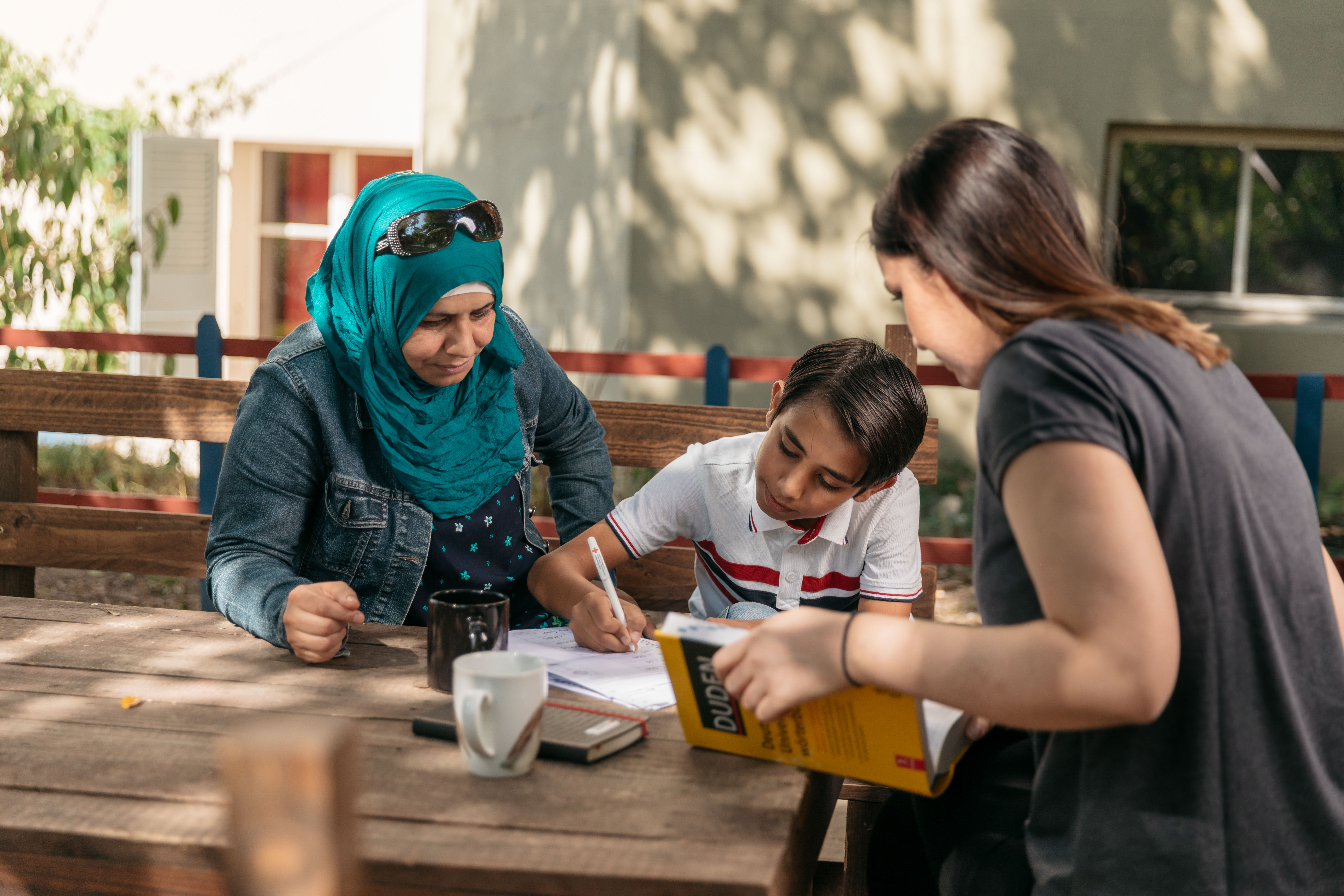 Eine Freiwillige unterrichtet eine Frau und ihren Sohn