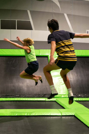 Two boys bouncing on trampolines