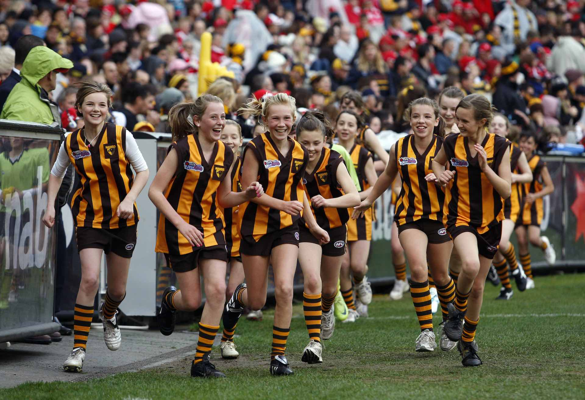 Girls with a smile on face are running at the boundary of footy stadium post-match