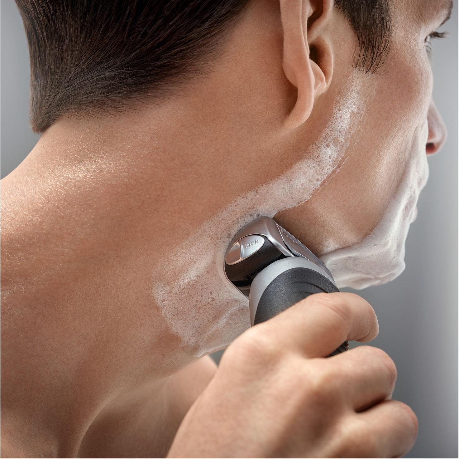 Braun Series 7 silver electric shaver in use