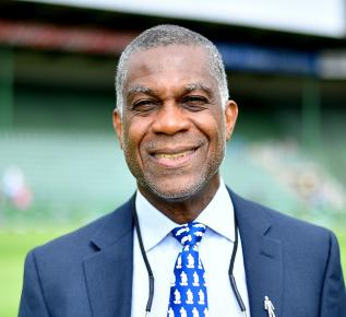"Whisper his name to cricket fans worldwide, and Michael is a gentleman who needs no introduction. A renowned Jamaican cricket commentator and former cricketer, Michael rose to fame through his legendary performances for the West Indies cricket team. Early in his Test career, Michael quickly showed himself to be a star of the sport when he broke the record for best bowling figures in a Test match by a West Indies bowler with 14 wickets for 149 runs. Seen as being one of the best fast bowlers ever to have played Test cricket, he was nicknamed """"Whispering Death"""" due to his quiet approach to the bowling crease. Since silently taking his last victim at the crease, Michael has gone from whispering to talking, spending the last 22 years as a Sky Sports cricket commentator."