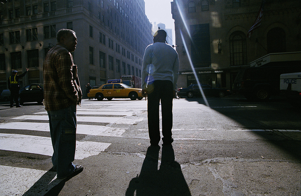 Two black men looking and waiting to cross the road, New York, USA