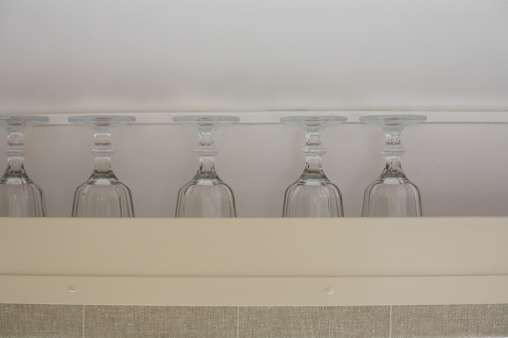 5 clear wine glasses sitting in row, upside down along a cream shelf against white wall