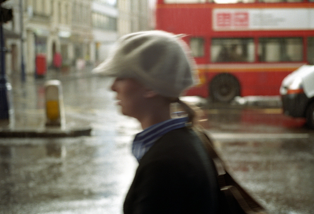 Blurred woman with white hat walking past. Oxford Circus, London, UK