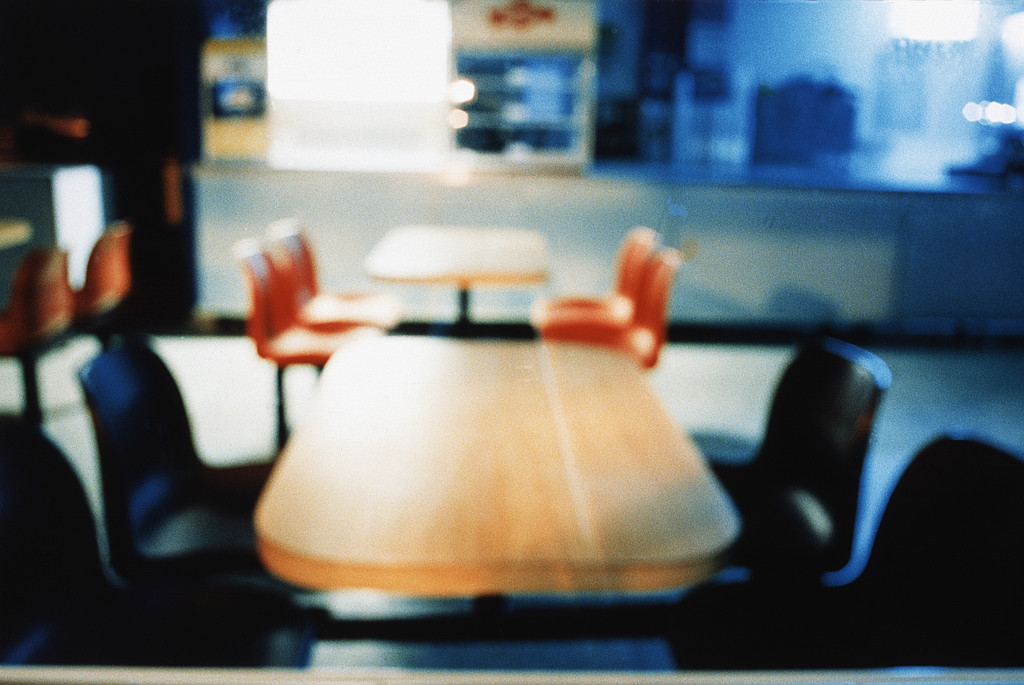Tables and chairs in a fast food at night