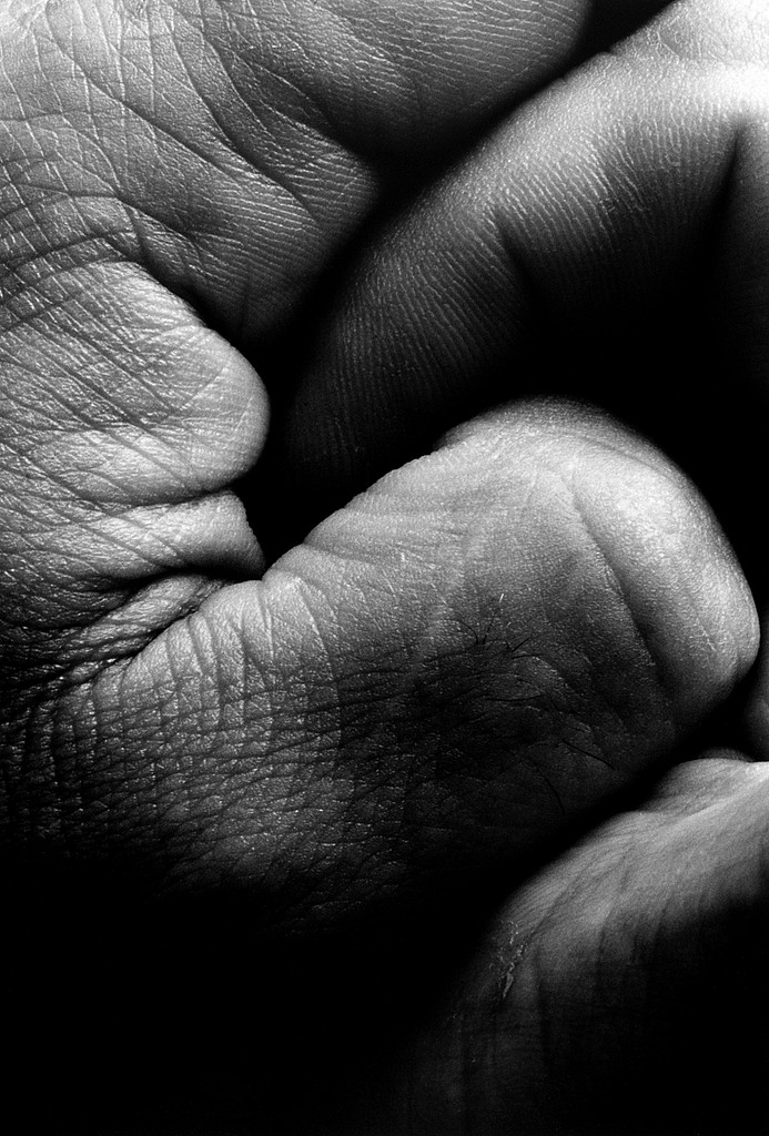Close-up of two hands closely entwined thumb cupped