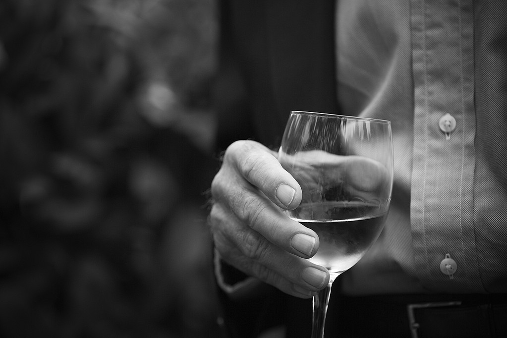Close up of mans hand holding a wine glass with white wine