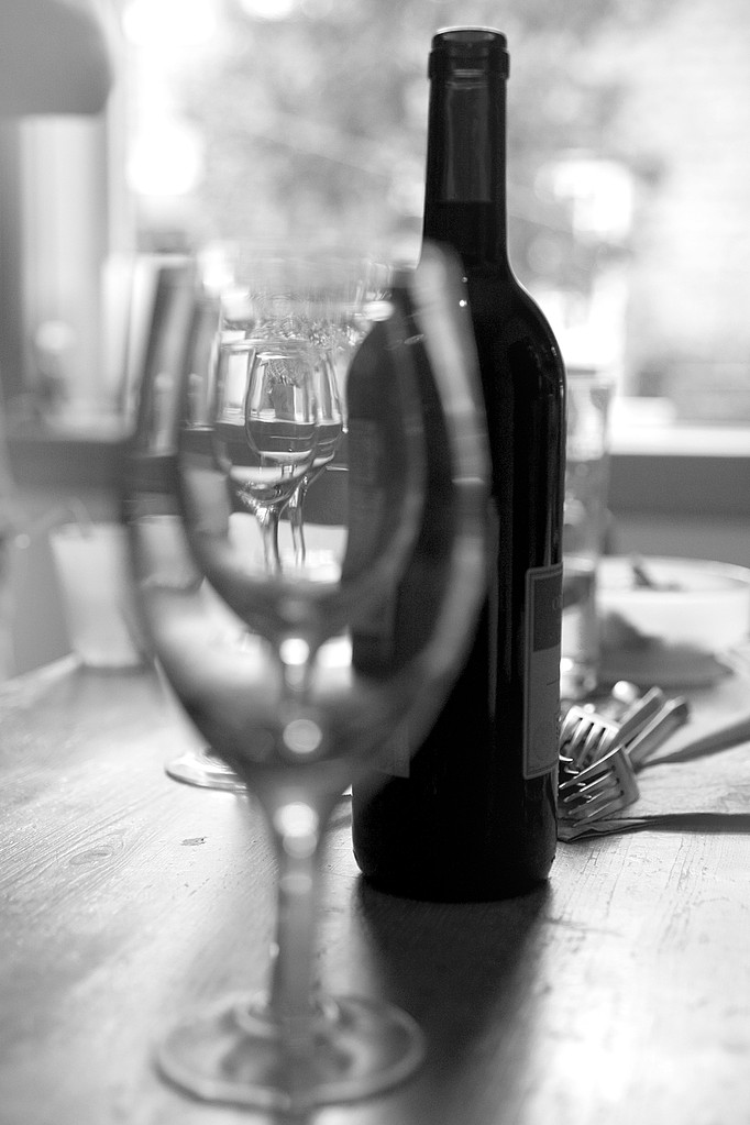 Wine bottle and glasses with cutlery on table