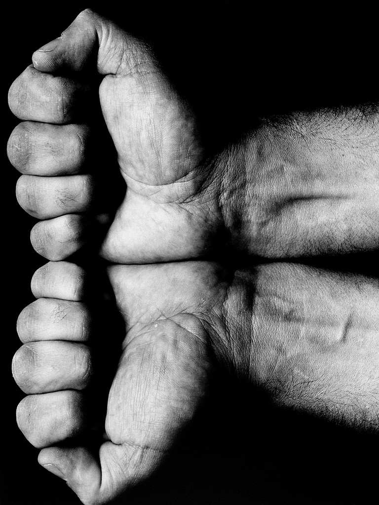 Two fists pressed together, with fingers curled forwards