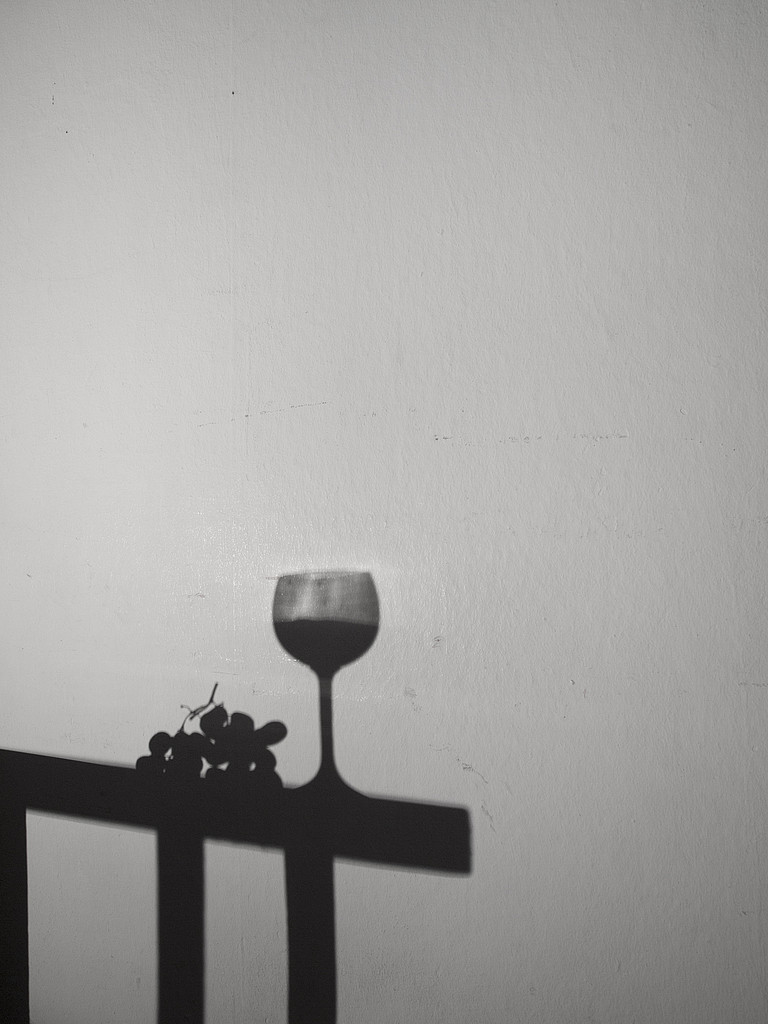 Shadow cast on white wall by table with wine glass and grapes