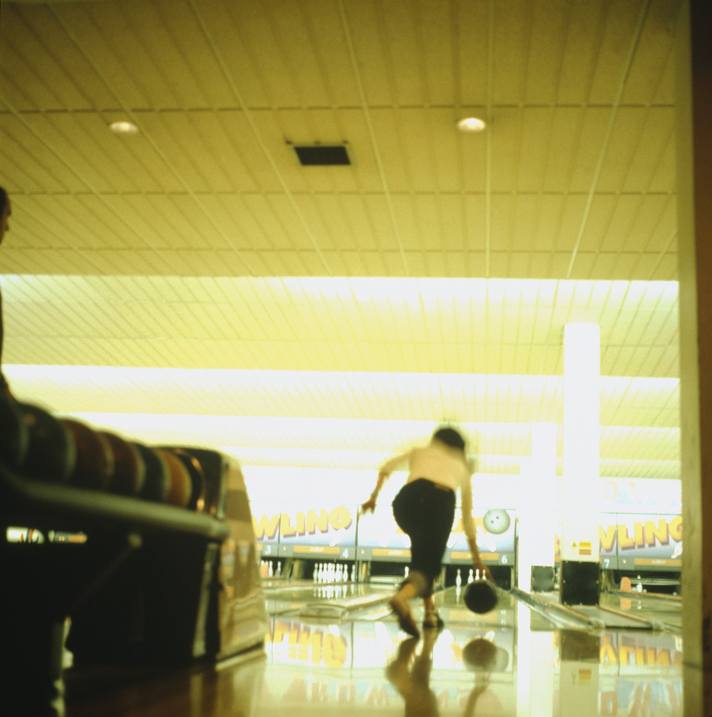 Woman seen from behind throwing ball down bowling alley, London, UK,
