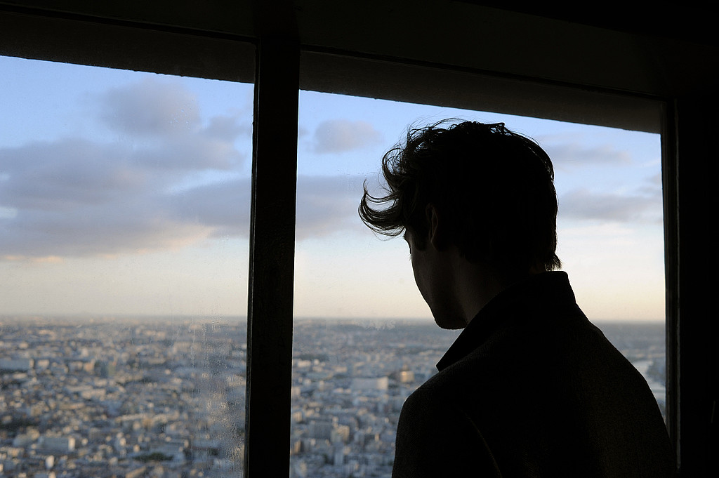 Portrait behind silhouetted young man in front of window looking down across the Paris skyline at dusk. Paris, France