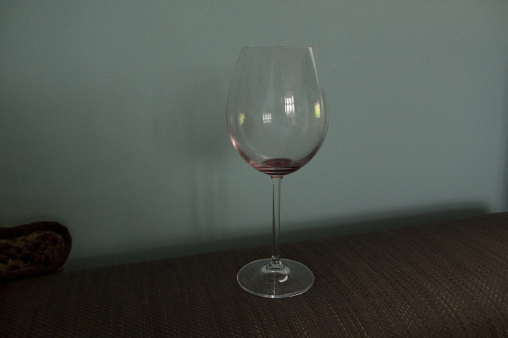 Almost empty red wine glass on sofa