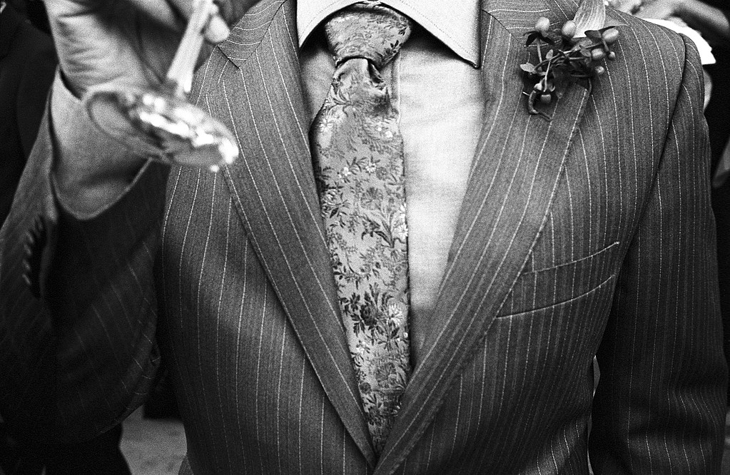 Chest of man in suit and tie drinking from champagne glass. Los Angeles, California, USA. October, 2007