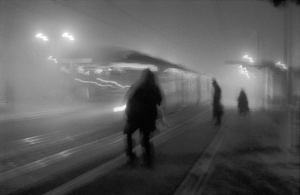 Train station on misty morning with shadowy figures and platform lights, West Hampstead, North London, London, UK