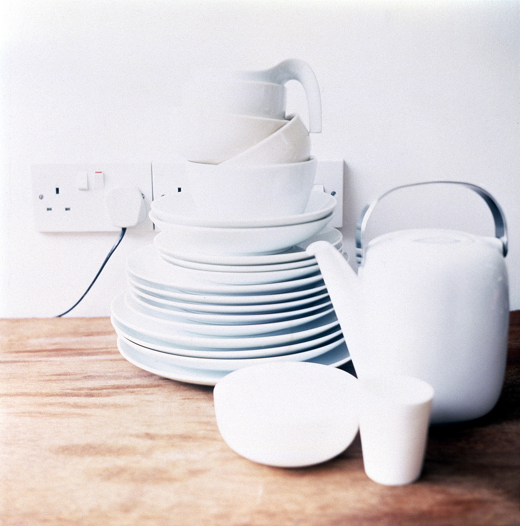 Pile of white porcelain dishes on wooden kitchen board with tea pot, electric socket and plug