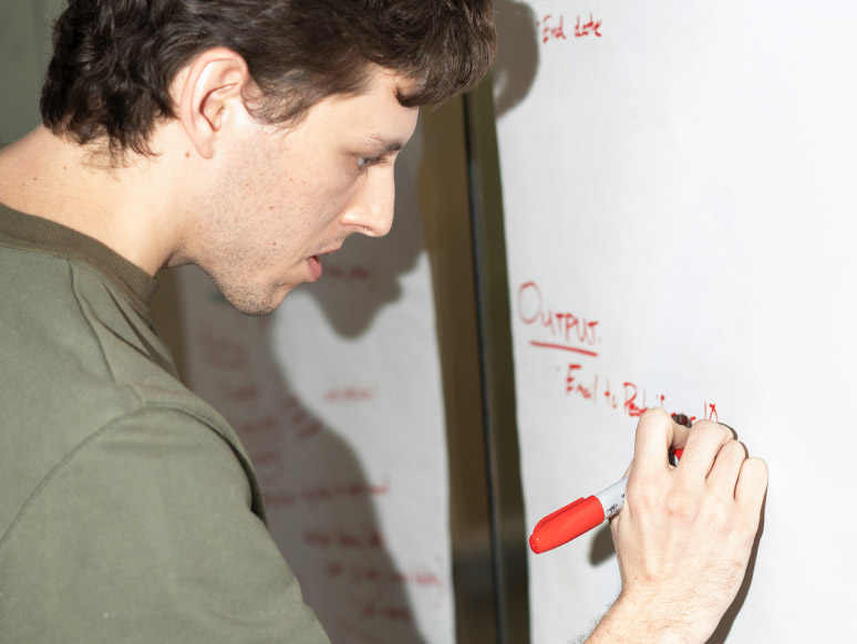 Picture of a man writing on a dry-erase board with red marker