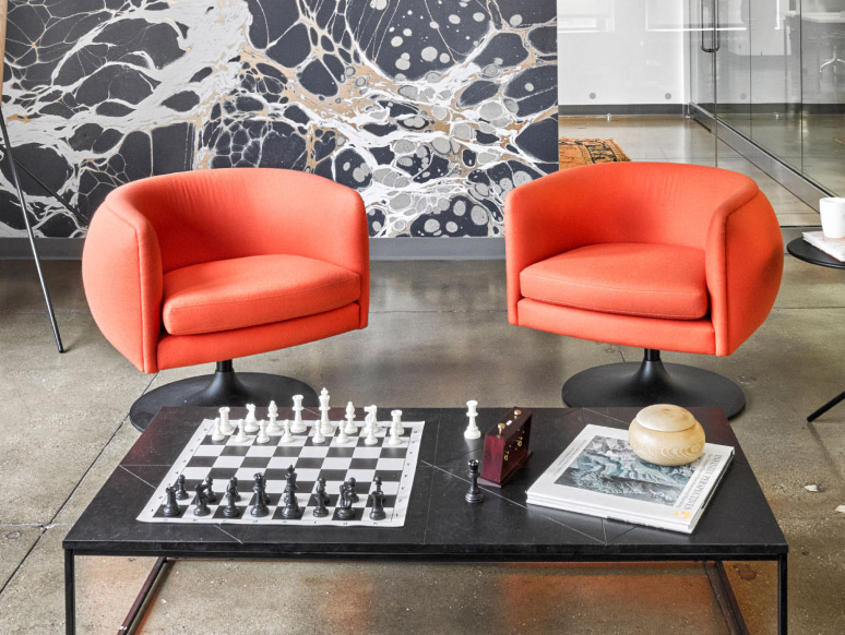Picture of a coffee table with a chess board and two orange chairs
