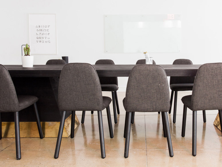 Picture of grey chairs at a black conference table