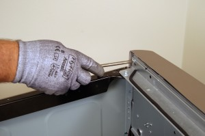 PHOTO: Remove the screw on the back of the control panel.
