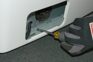 PHOTO: Reinstall the screw at the base of the washer in the pump housing opening.