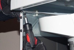 Remove the screw from under the left front corner of the top panel.