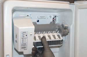 Lower and flip the ice maker to access its wiring harness.