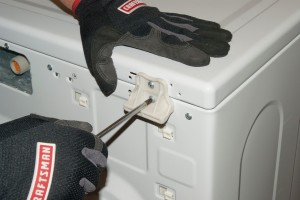 Remove the top panel screws at the back of the washer.