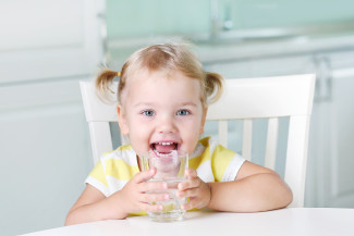 Smiling girl drinking glass of water