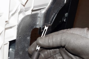 PHOTO: Remove the tension spring from the door hinge.