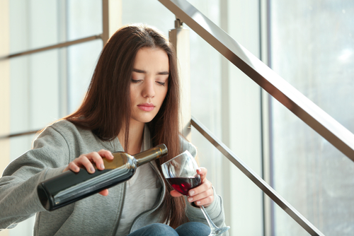 sad woman pouring herself a glass of red wine
