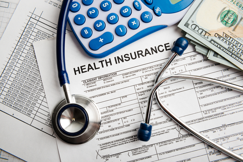 insurance forms, stethoscope, calculator and money