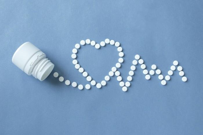 white pills spilled into heart shape