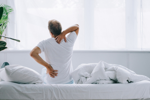 man getting out of bed with back pain