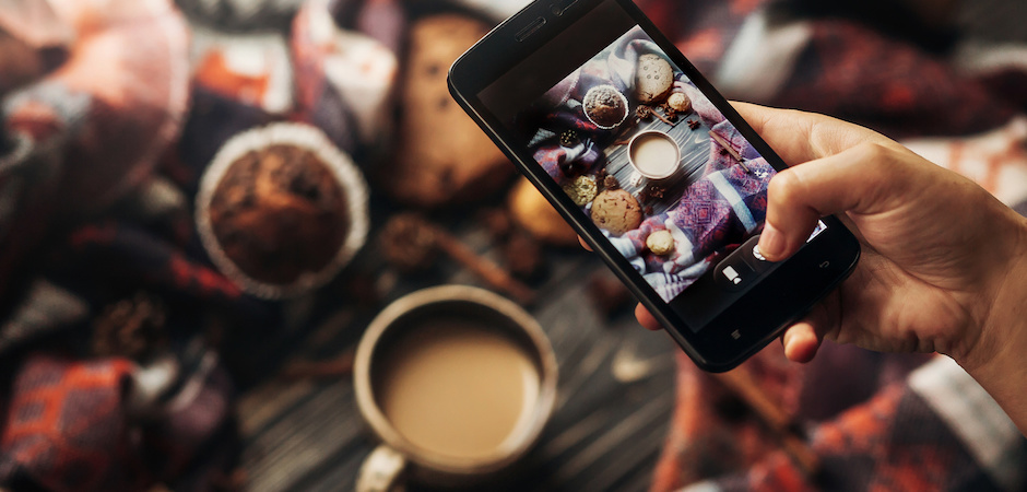 instagram photography blogging workshop concept. hand holding phone taking photo of stylish winter flat lay coffee cookies and spices on wooden rustic background. cozy mood autumn