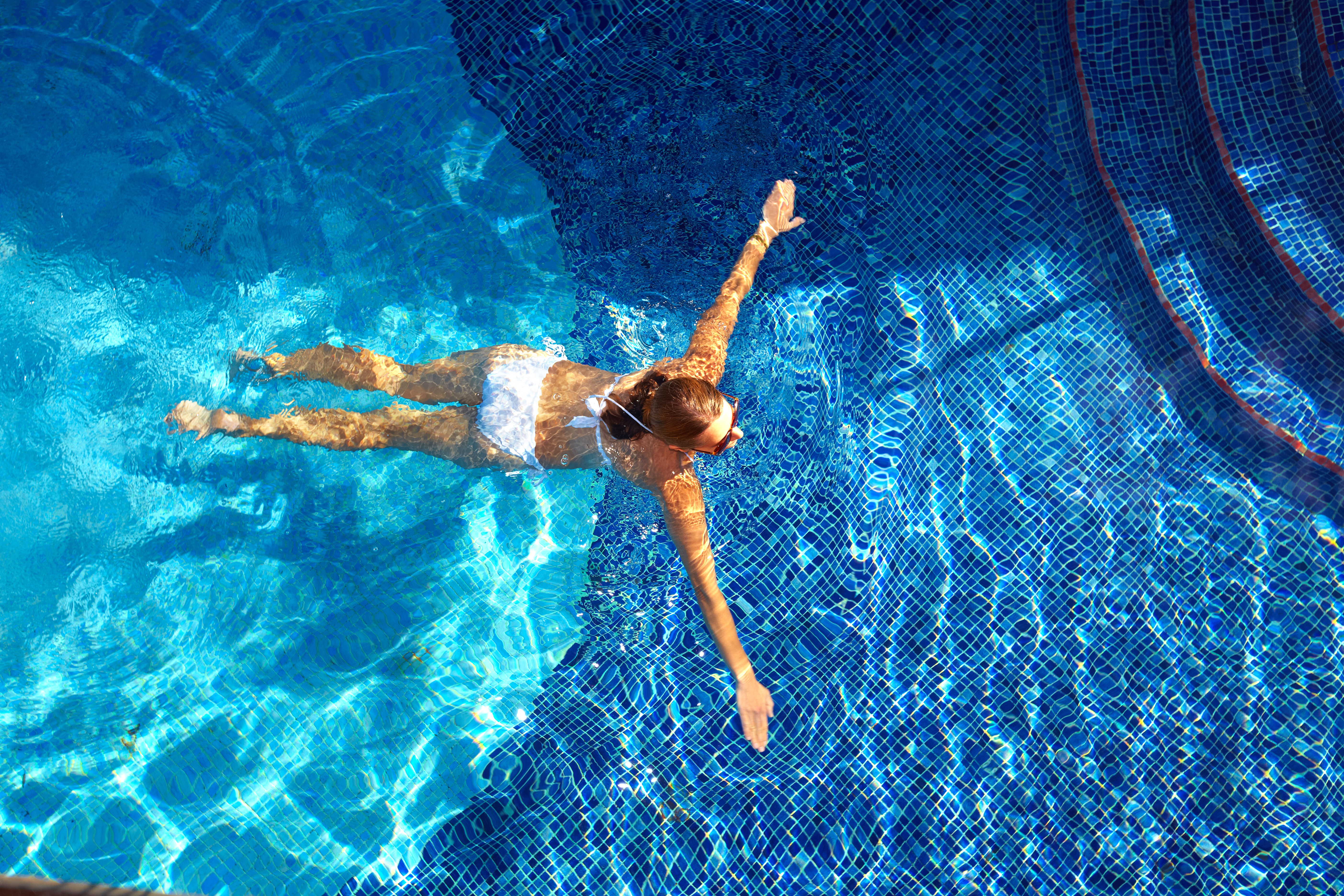 girl swimming in crystal clear mineral pool
