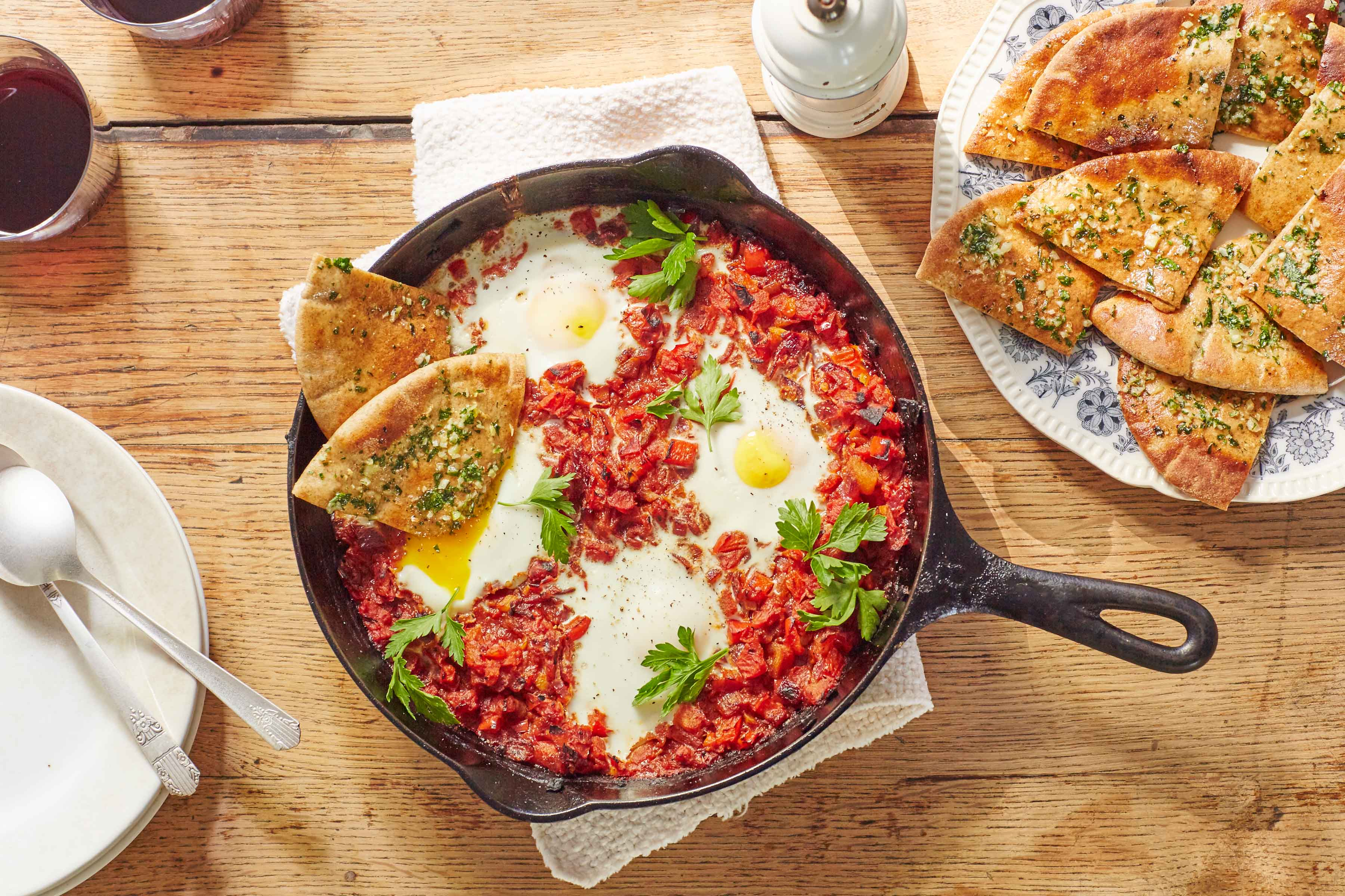 Shakshuka, a Middle Eastern tomato and egg dish, baked in a cast iron skillet with a plate of toasted pita cut in triangles and topped with herbs on the side