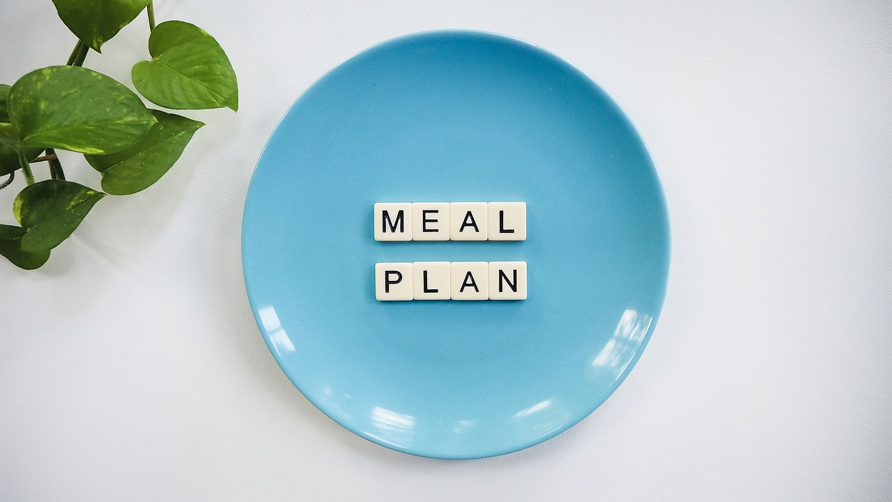Meal Plan written in Scrabble letters in the middle of bright blue plate