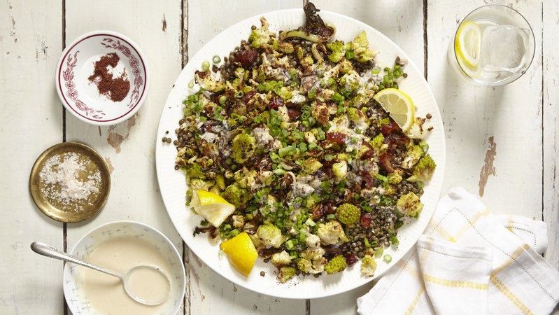 Hearty salad with lentils and roasted vegetables and lemon wedges on a large white platter against a white wooden background