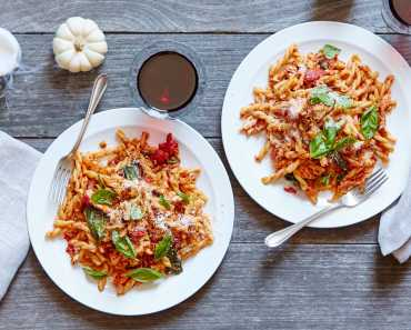 spicy chicken pasta with crispy chicken skin and basil