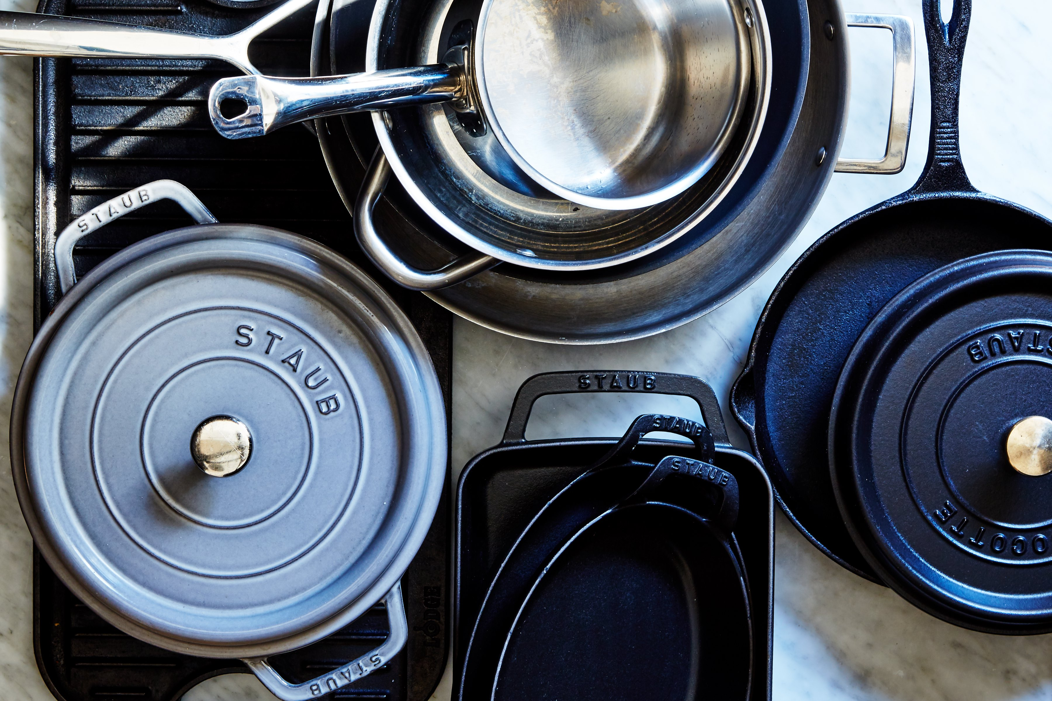 overhead shot of many stainless steel and cast iron pots, pans, and dutch ovens on a stove