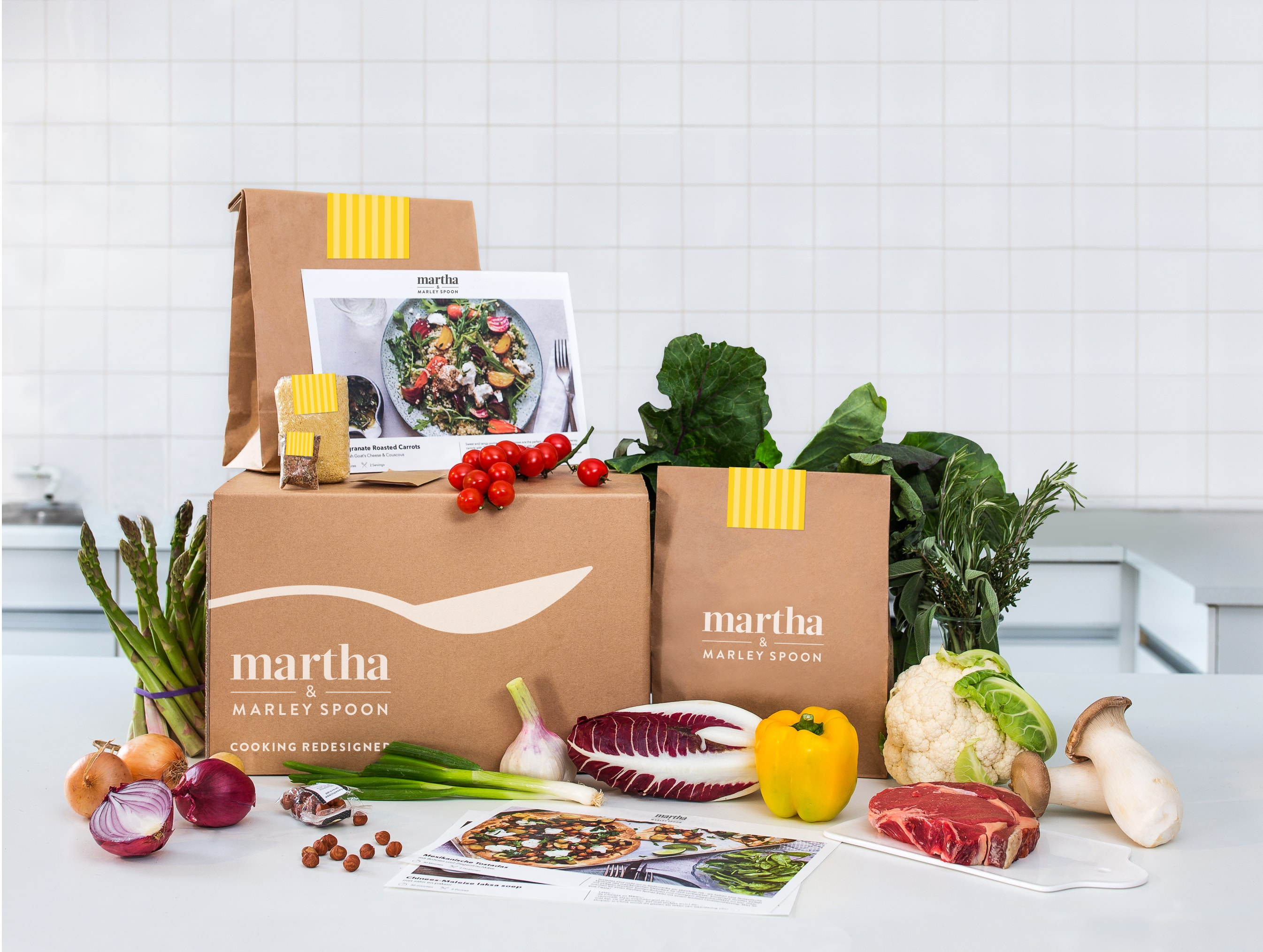 Martha and Marley Spoon food subscription box with fresh ingredients on a white table.