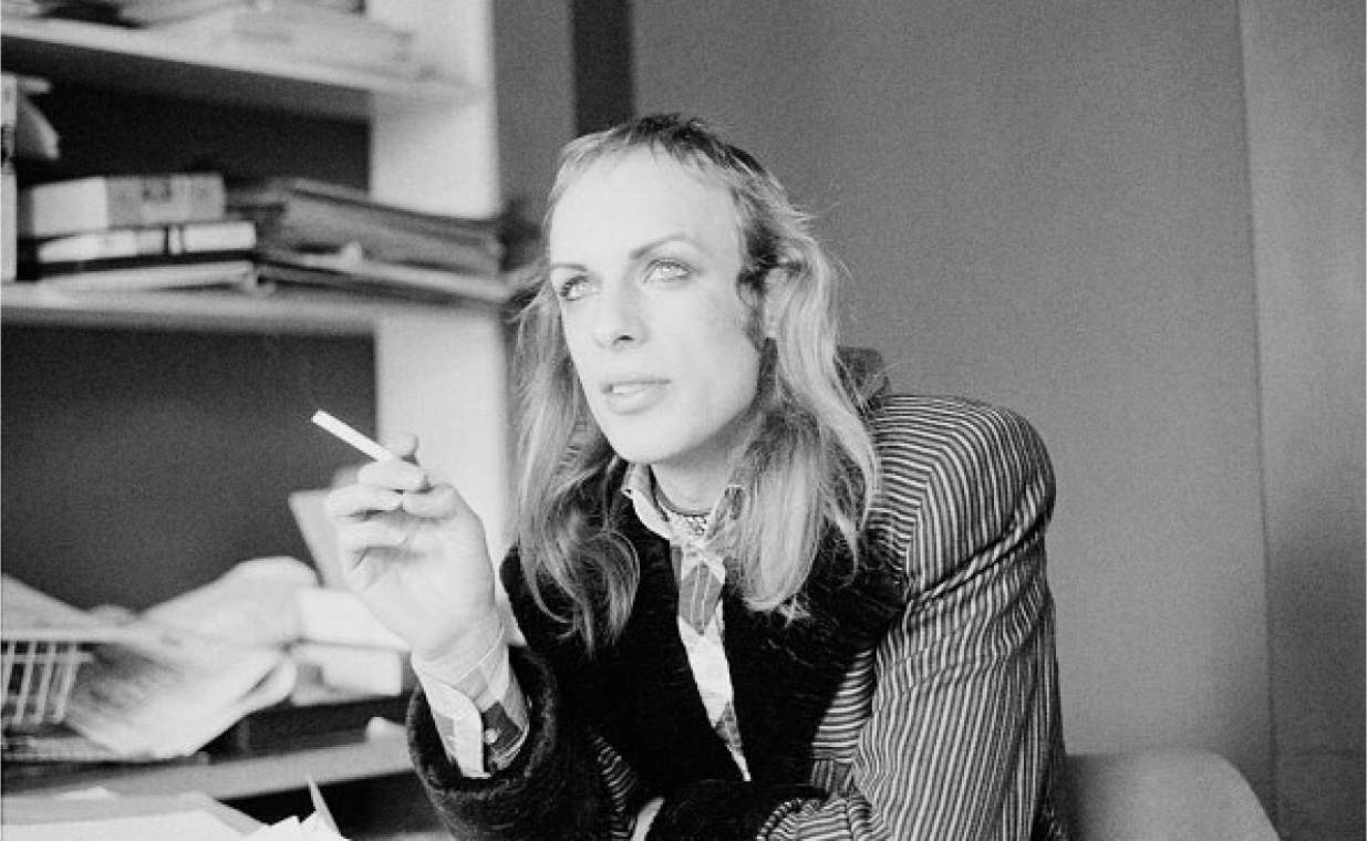 Brian Eno sitting in an office with a cigarette, looking into the distance