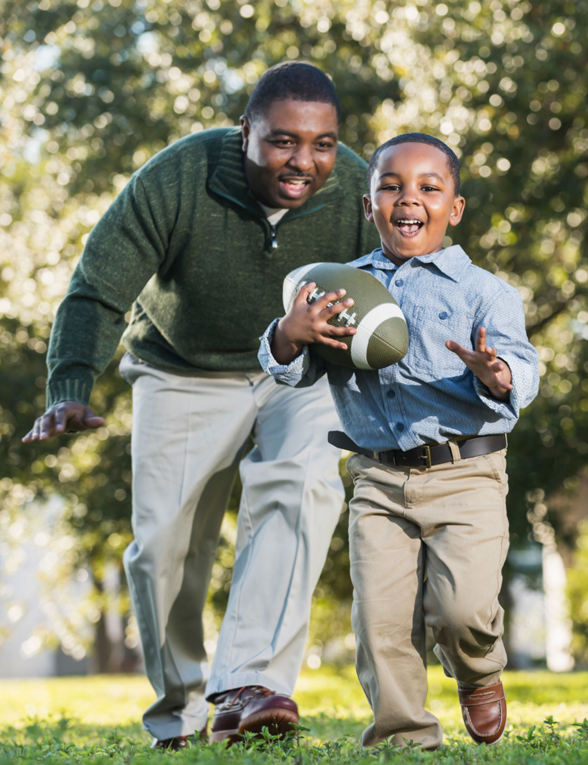 An African-American father and young son play football on their lawn.