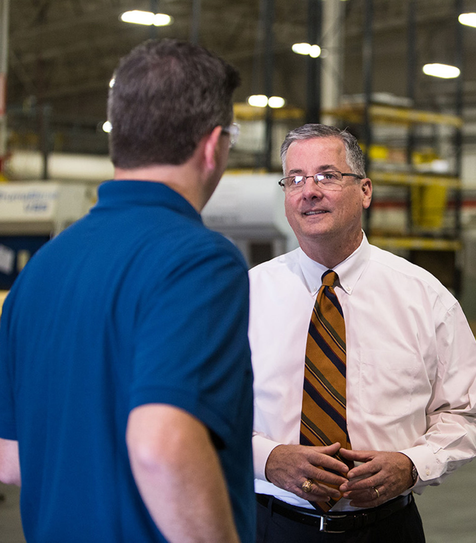 Executive VP Jim Johnson chats with a customer on floor of his factory.